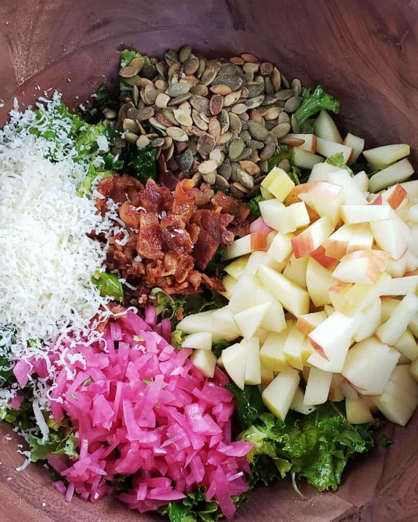 kale salad ingredients in a wooden bowl