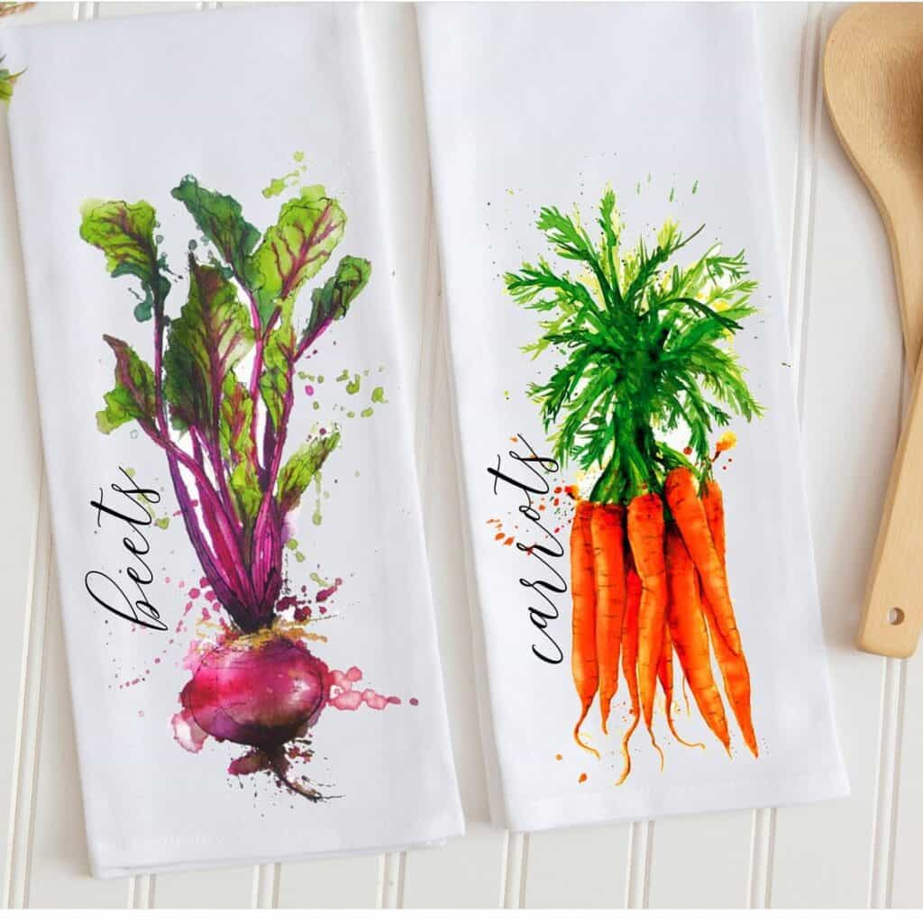 two watercolor printed tea towels with beets and carrots printed on them