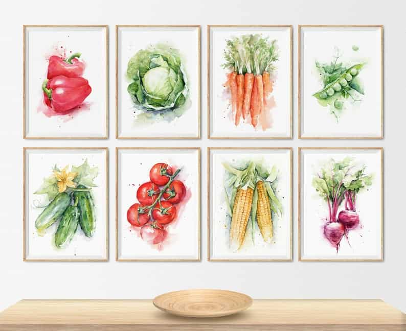 set of eight watercolor vegetable prints hanging on a wall