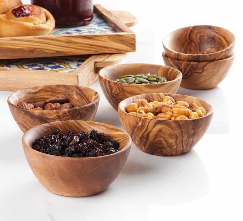 small wooden bowls filled with nuts, seeds, and dried fruit