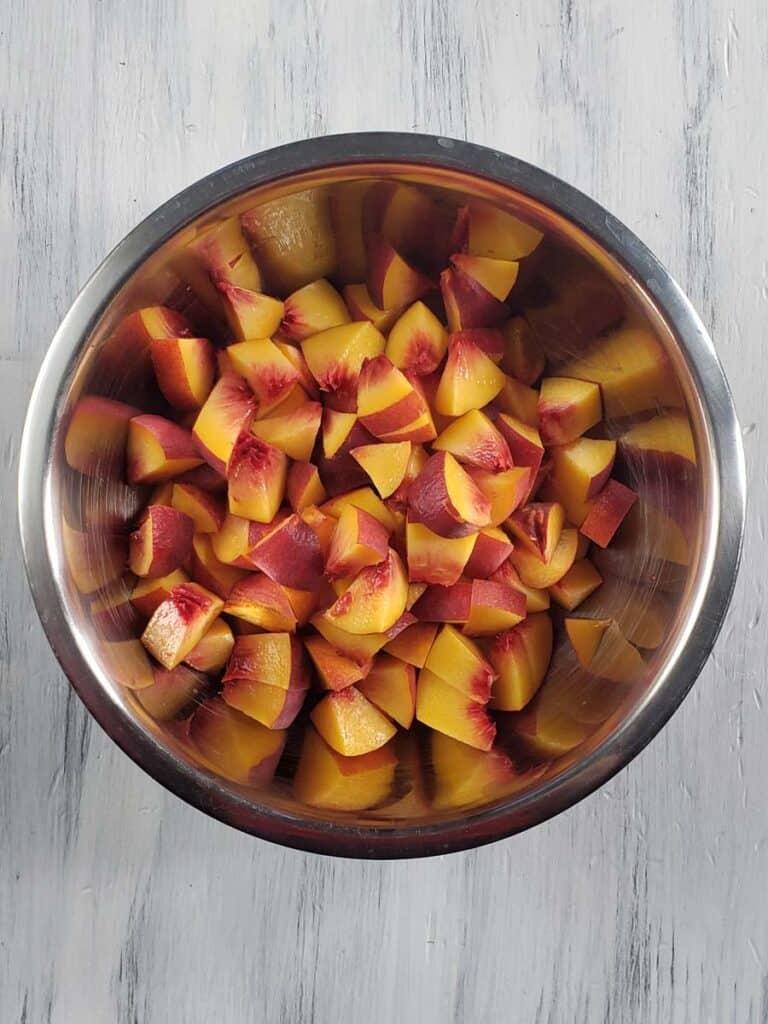 diced peaches in a metal bowl