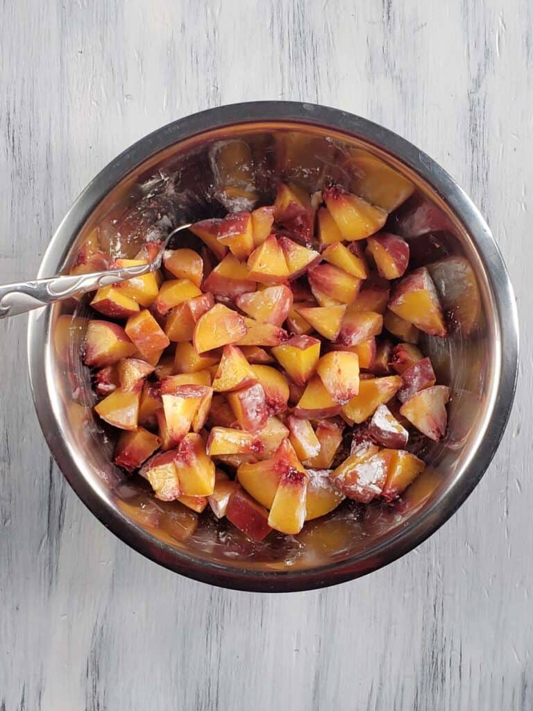 diced peaches coated with cornstarch in a metal bowl