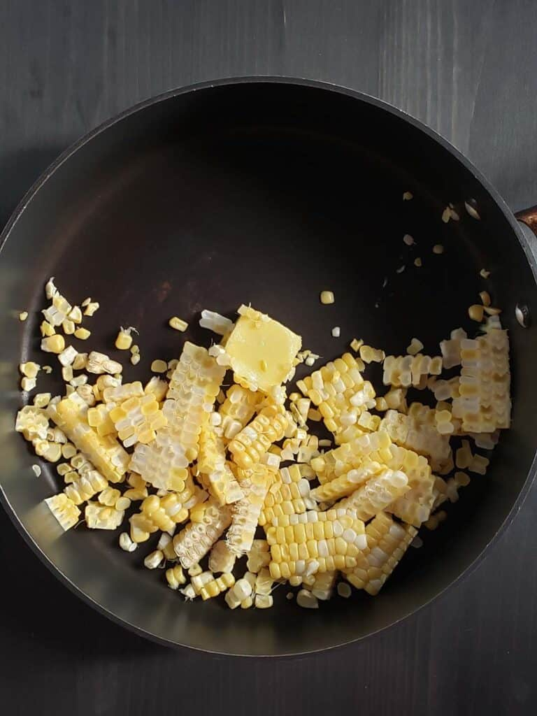 uncooked corn and butter in a sauce pan
