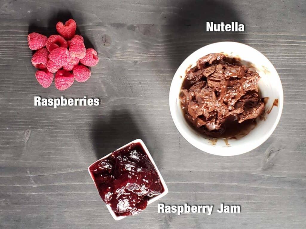 Raspberries Nutella and Raspberry Jam on a dark surface