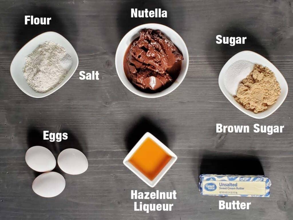 Raspberry Nutella Brownie Ingredients on a dark surface